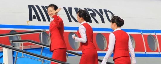 Azafatas saludando mientras entran en un avión de Air Koryo
